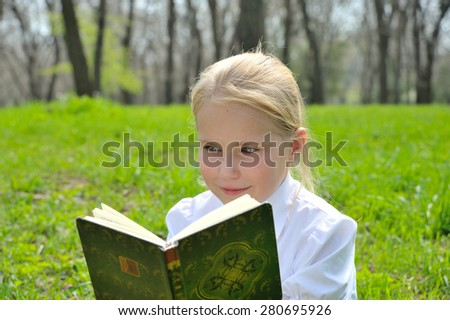 Adorable cute little girl reading book sitting outside on grass - stock photo