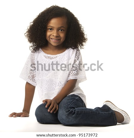 Adorable cute little girl sitting down isolated against white