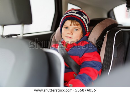 Adorable cute preschool kid boy sitting in car in winter clothes. Little child in safety car seat with belt enjoying trip and jorney. Safe travel with kids and traffic laws concept.