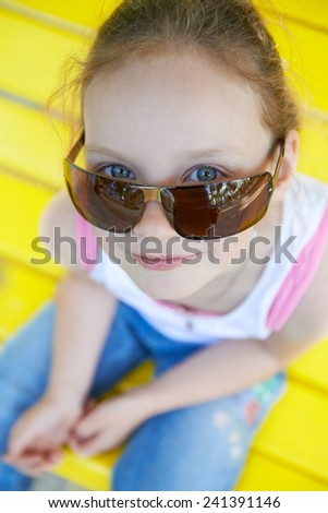 Adorable cute pretty little gir in sunglasses playing outdoors in summer. Happy childhood - stock photo