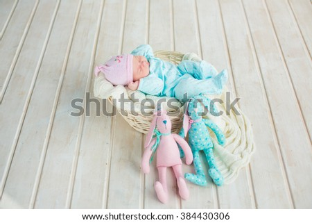 adorable cute sweet baby girl sleeping in white basket on wooden floor with two toy tilda rabbits  - stock photo