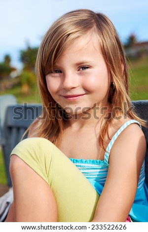 Adorable cute young girl child smiling portrait outdoors with blonde hair - stock photo
