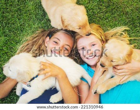 Adorable Cute Young Girls Playing and Hugging Puppies - stock photo