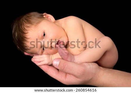 Adorable 7 days old baby sucking on his own toe - stock photo