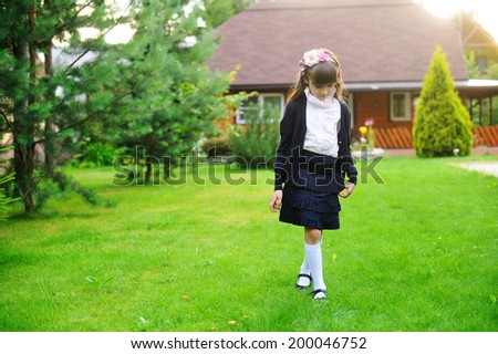 Adorable elegant  kid girl in navy and rose  school uniform staying on the lawn after school  - stock photo