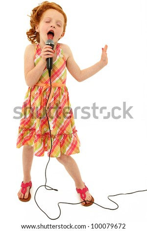 Adorable elementary age school girl singing into microphone isolated over white background.