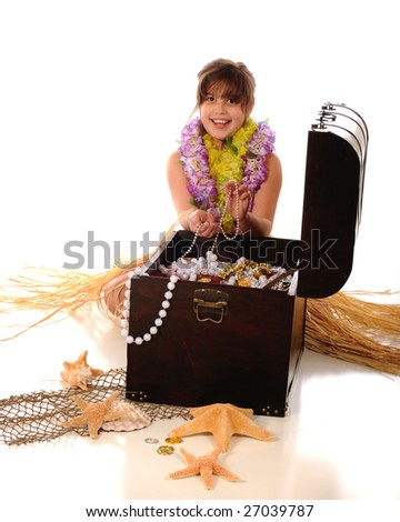 Adorable elementary girl in a Hawaiian grass skirt and leis, delighted with the treasures she's found in an old pirate chest.  Isolated on white. - stock photo