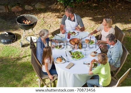 Adorable family eating in the garden - stock photo
