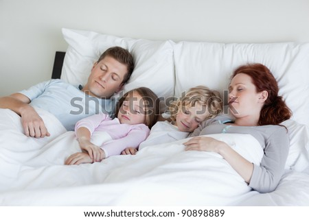 Adorable family snoozing in the bed together - stock photo
