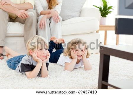 Adorable family watching tv in the living-room - stock photo