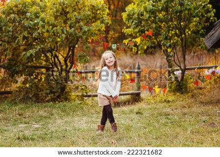 Adorable fashion kid playing in the park. Autumn concept