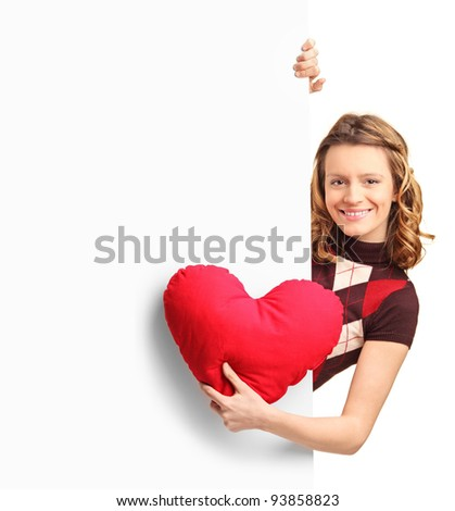 Adorable female peeking out of a banner with a red heart in her hand - stock photo
