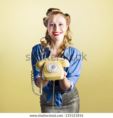 Adorable female pinup model holding olden day rotary phone in a call us now concept on yellow gradient background - stock photo