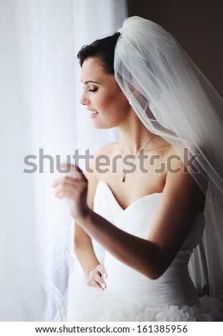 Adorable fiancee waiting for the groom. Young brunette bride in the morning at home. - stock photo