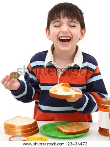 Adorable five year old boy making peanut butter and jelly sandwich. - stock photo