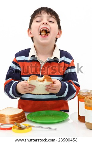 Adorable five year old boy making peanut butter and jelly sandwiches. - stock photo