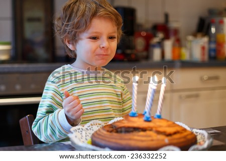 Adorable four year old boy celebrating his birthday and blowing off the candles on the cake, indoor - stock photo