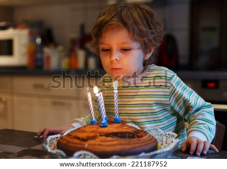 Adorable four year old kid boy celebrating his birthday and blowing off the candles on the cake, indoor - stock photo