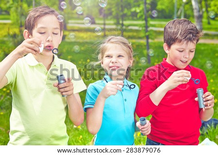 Adorable friends blowing soap bubbles in park - stock photo