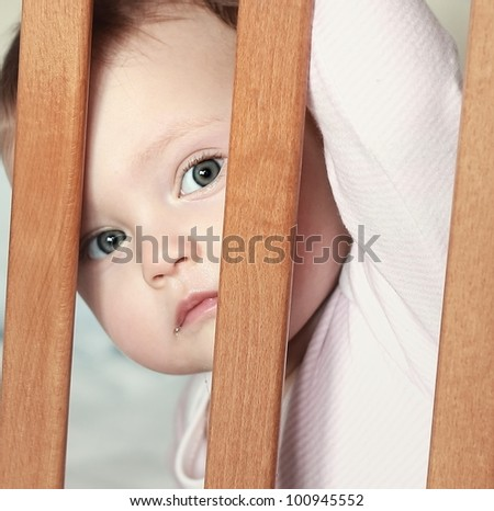 Adorable funny baby boy looking out the wooden bed with big eyes