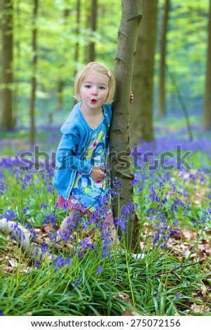 Adorable funny child, blonde healthy toddler girl enjoying nature, playing, hiking and hiding behind the tree in spring or summer forest with bluebells flowers - stock photo