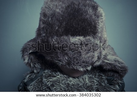 Adorable, Funny child with fur hat and winter coat, cold concept and storm