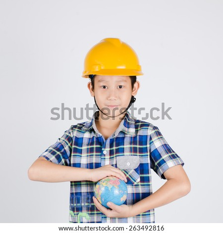 Adorable future builder constructing the world a over gray background. - stock photo