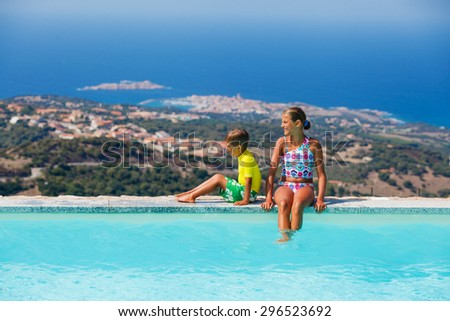 Adorable girl and little boy relaxing at swimming pool with sea view - stock photo