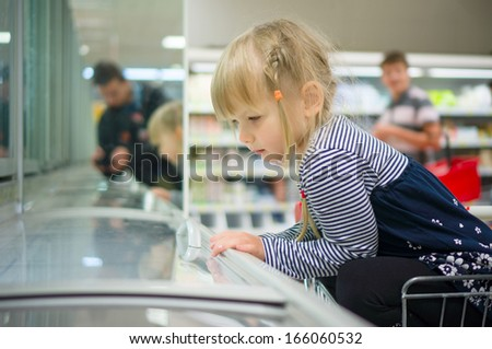 Adorable girl at shopping cart select ice cream in supermarket - stock photo