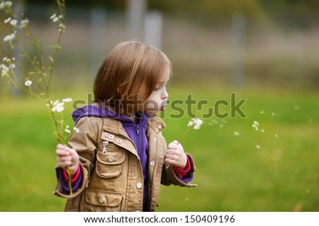 Adorable girl blowing off dandelion on late autumn day - stock photo