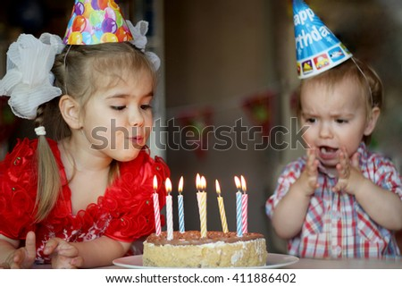 Adorable girl blowing out the candle on her birthday cake with surprised brother on the background, happy birthday concept - stock photo
