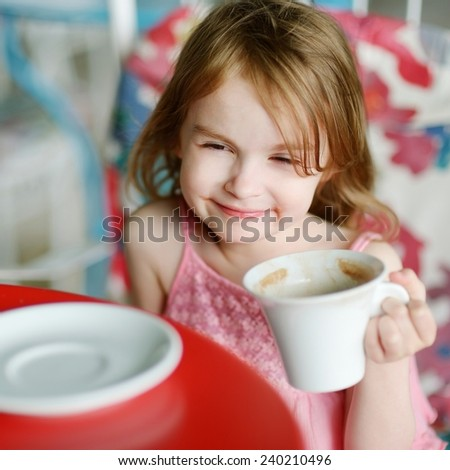 Adorable girl drinking hot chocolate in outdoor restaurant - stock photo