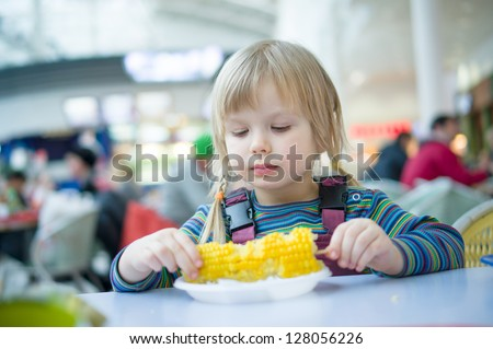 Adorable girl eat corn on stick in fast food restaurant
