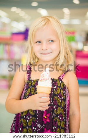 Adorable girl eat fruit ice cream in mall - stock photo