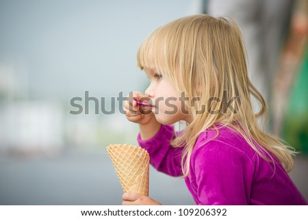 Adorable girl eat ice cream near mall - stock photo