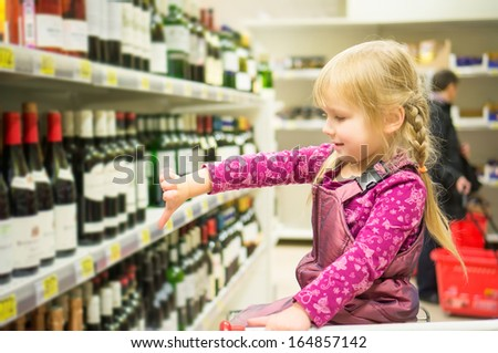Adorable girl grimacing sitting in shopping cart in alcoholic beverages department in supermarket