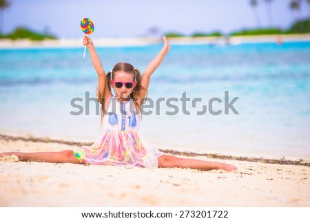 Adorable girl have fun with lollipop on the beach - stock photo