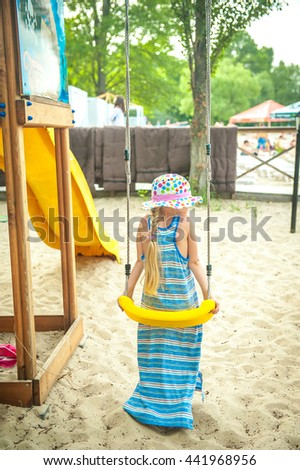 Adorable girl having fun on a swing on playground on the beach on summer day - stock photo