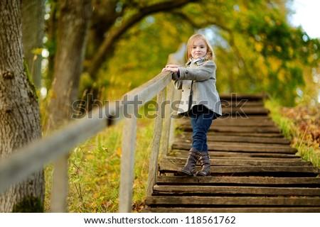 Adorable girl having fun on beautiful autumn day - stock photo