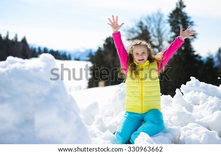 Adorable  girl holding Christmas baubles in hands in winter forest