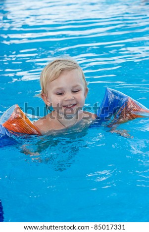 Adorable girl in armbands in swimming pool outdoor - stock photo