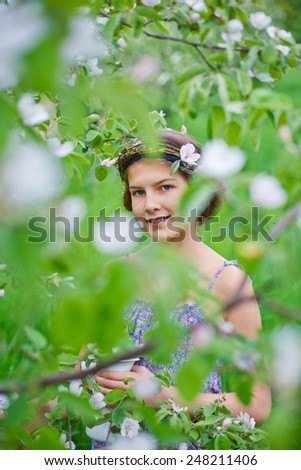 Adorable girl in blooming apple tree garden on spring day - stock photo