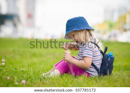 Adorable girl in blue hat eat ice cream sitting on grass - stock photo