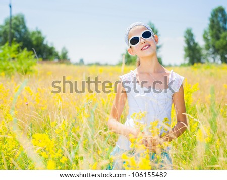 Adorable girl in glasses with flowers in yellow field. Summer freedom andjoy concept. - stock photo