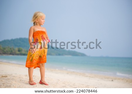 Adorable girl in orange dress stay on high sand ocean beach - stock photo
