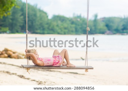 Adorable girl in pink swimming suit lie down on swing on the beach - stock photo