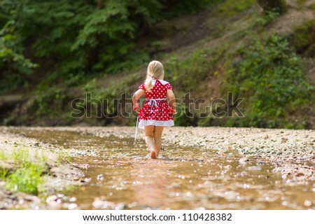Adorable girl in red dress walk in small river stream