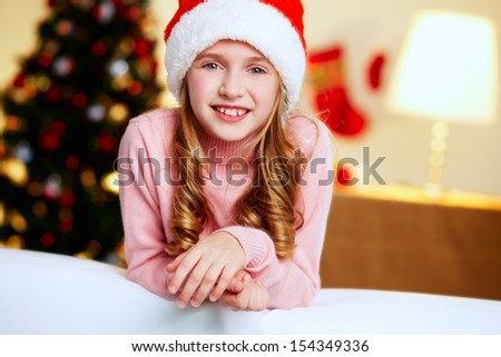 Adorable girl in Santa hat looking at camera - stock photo