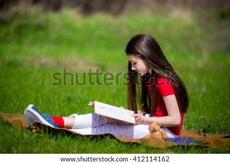 Adorable girl in summer park reading book. Adorable girl in summer park reading book - stock photo