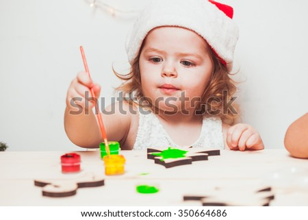 Adorable girl is painting wooden Christmas figurines - stock photo